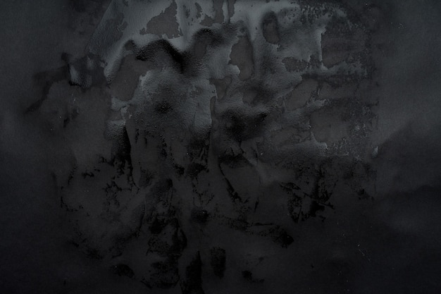 Wet black paper glued to the wall. wet paper texture.