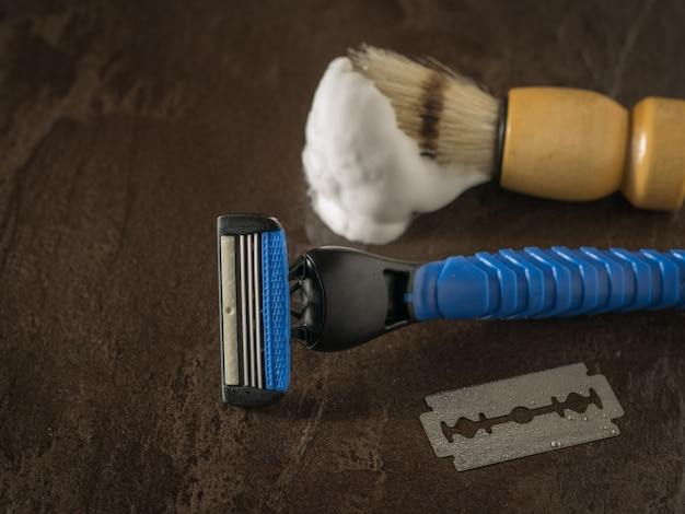 A wet blade, a blue razor, and a brush on a stone background. set for care of a man's face.
