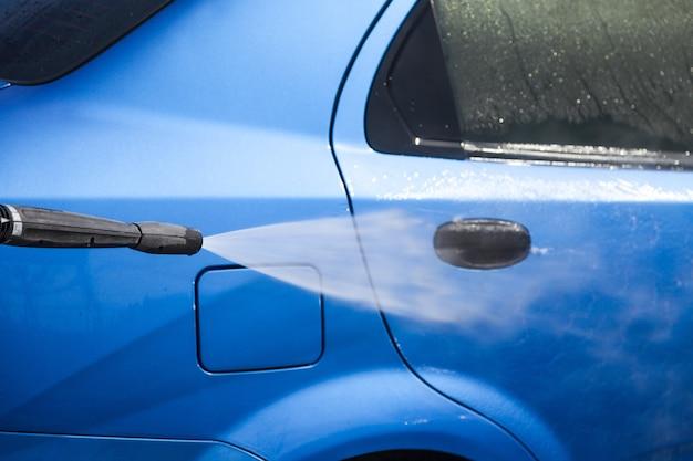 背景に濡れた青い車