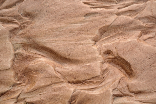 濡れた茶色の砂の自然のテクスチャ背景。上面図
