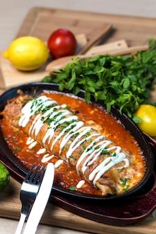 Wet burrito in tomato sauce garnished with cream