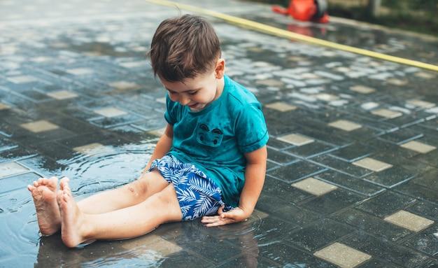 물이 바닥에 앉아 미소로 마당에서 놀고 젖은 백인 소년