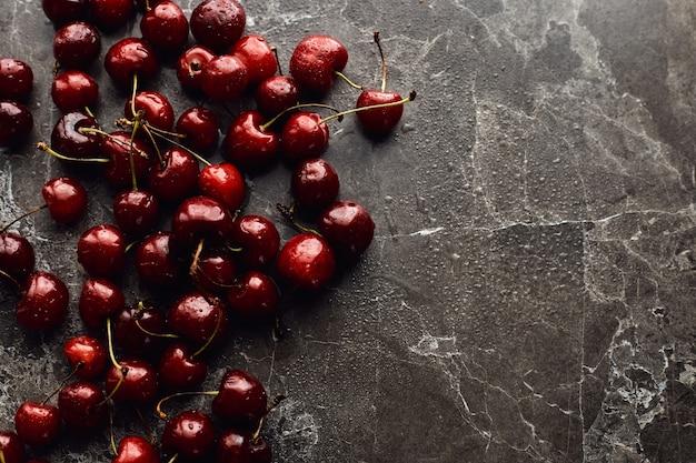 Wet cherries on dark rustic surface