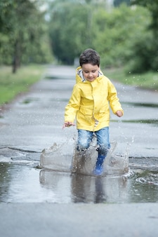 A wet child is jumping in a puddle.