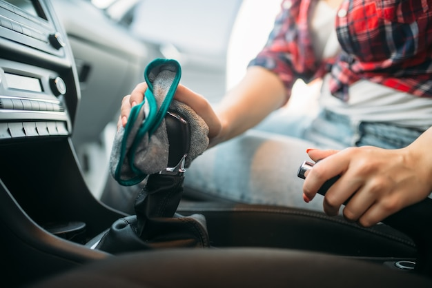 Влажная уборка салона автомобиля на автомойке. женщина на автомойке самообслуживания. уборка автомобилей на открытом воздухе в летний день