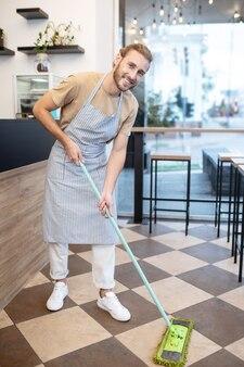 습식 청소. 좋은 분위기의 카페에서 젖은 청소를하고 걸레와 젊은 성인 수염 난된 남자