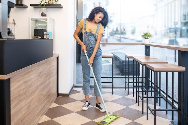 ウェットクリーニング。午後にカフェで床を徹底的に拭くムラートの女性を笑顔の若い大人