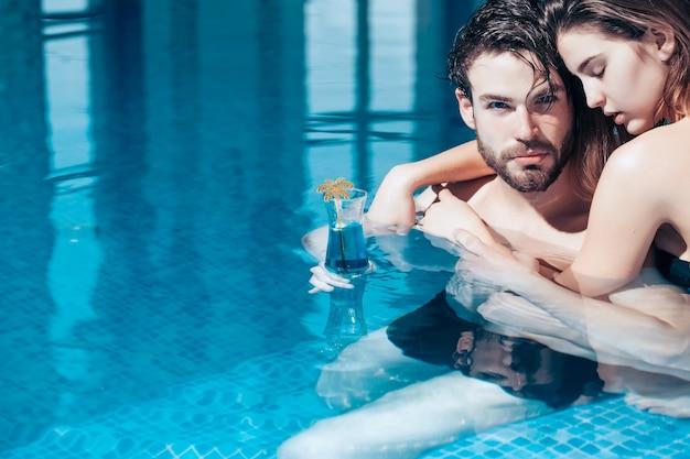 Влажная пара красивой женщины или сексуальной девушки и красивого бородатого мужчины или парня с мускулистым телом в бассейне с голубой водой держит бокал для коктейля, копирование пространства