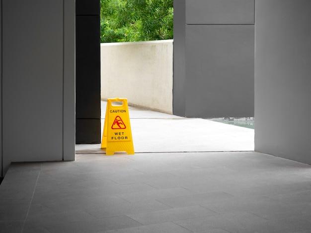 Предупреждающий знак о мокром полу на дорожке возле здания после дождя
