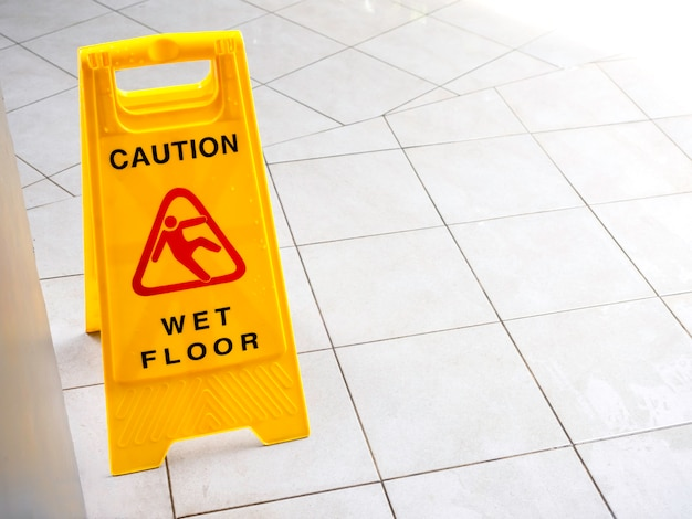 Wet floor caution sign on the walkway near the building after raining