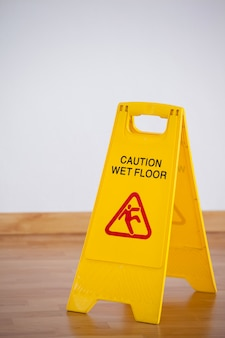 Wet floor caution sign on wooden floor