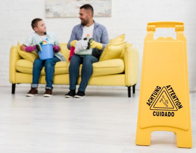 Segno del pavimento bagnato con uomo e ragazzo defocused