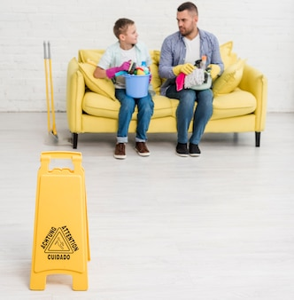 Segno del pavimento bagnato con uomo e ragazzo sul divano