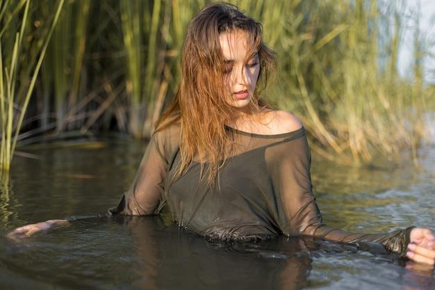 葦、水中の少女の感情的な肖像画と水中で濡れた女の子