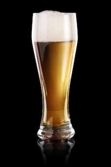 黒の背景に分離された新鮮なビールのウェットグラス