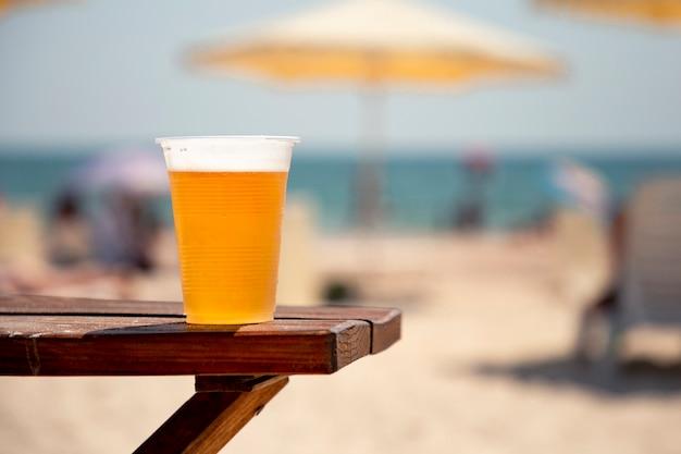 海の岸に木製のテーブルの上の黄金のビールのぬれたガラス