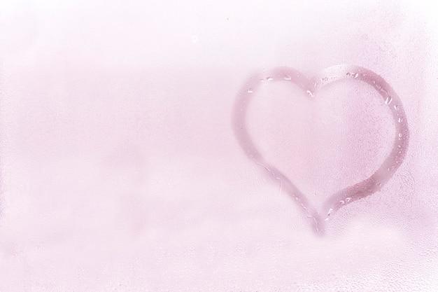濡れたガラスの質感。石碑に指で描かれたハート。明るいロマンチックな背景