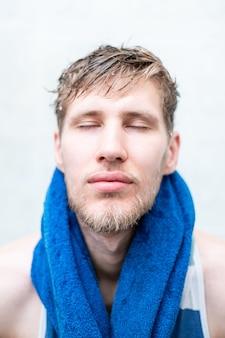 自宅でシャワーを浴びた後、濡れた男性の髪とタオルを持っています