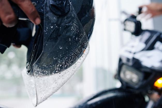 Мокрое стекло шлема мотоциклиста