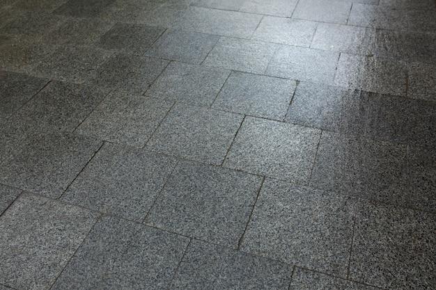雨上がりの大理石のチップでできた濡れた舗装スラブ。リヴィウ、ウクライナ
