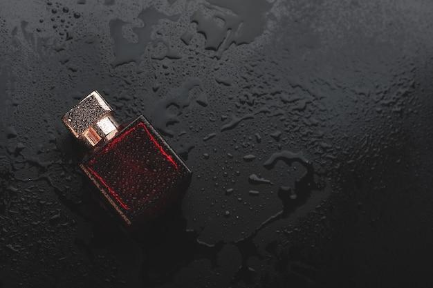黒の背景に濡れた香水