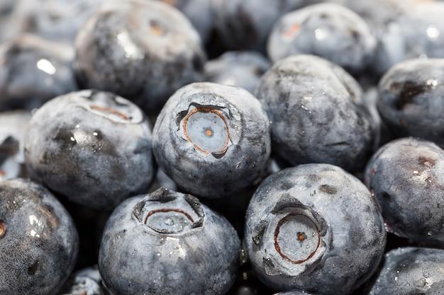 木製のテーブルに濡れた熟したジューシーでおいしいブルーベリー、ブルーベリーベリーは水滴で覆われています、ウェットベリーは生で食べたりデザートを作ったりするのに使用できます