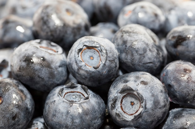 Wet ripe juicy and tasty blueberries on a wooden table, blueberry berries are covered with water drops, wet berries can be used to eat raw or make desserts