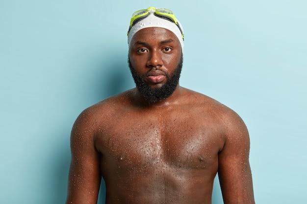 Мокрый серьезный темнокожий мужчина носит очки на лбу, позирует голым, имеет пухлые губы