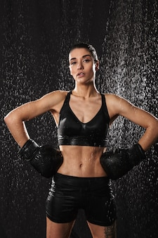 Wet sexual woman putting arms in boxing gloves on waist and looking on camera under rain drops, isolated over black background