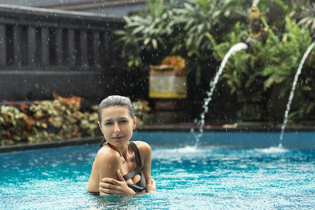 Wet sexy blackhair woman in swimsuit posing at pool.