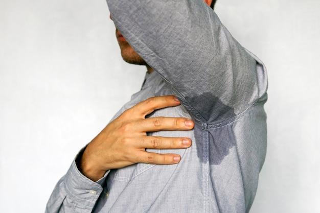 내 파란색 셔츠에 땀에 젖은 반점. 파란색 배경에서 불쾌한 냄새를 풍기는 남자.