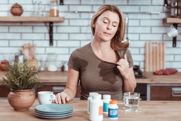 ウェットスポット。水をこぼして薬を飲みすぎた後、tシャツに濡れた斑点がある金髪の女性
