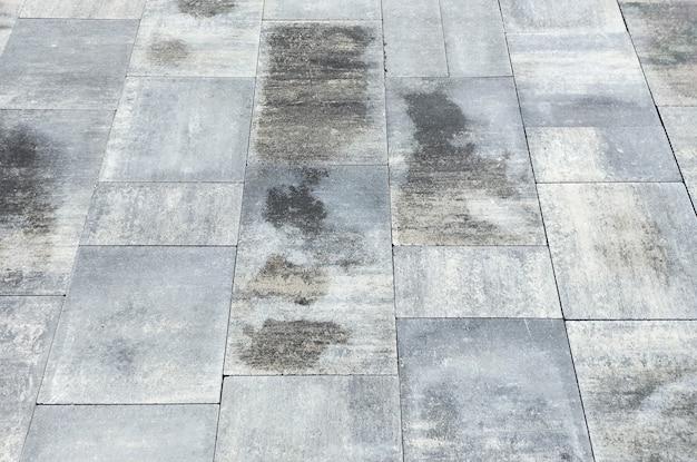 Мокрая дорога мощеная камнем. серый фон текстуры плитки.