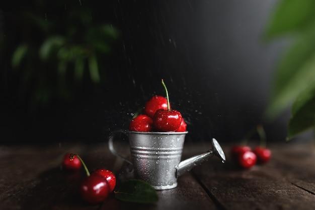 流れる水の流れと滴と木製の背景テーブルの上の小さなじょうろで濡れた甘いチェリーベリー。鮮度、夏のコンセプト。コピースペースエリアでのエコ、バイオファームフルーツ収穫。ローキー