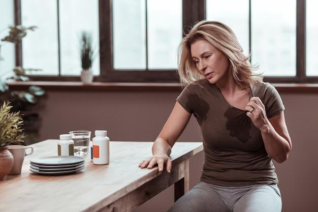 ぬれたtシャツ。汗をかいて濡れた t シャツを持っている金髪のストレスと落ち込んでいる女性