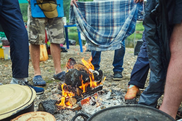 젖은 관광객은 캠프 파이어 주변을 하이킹하고 옷을 말립니다.