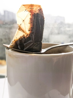 白い汚れたセラミックカップの上に横たわっている金属のスプーンに濡れた使用済みの使い捨てティーバッグ