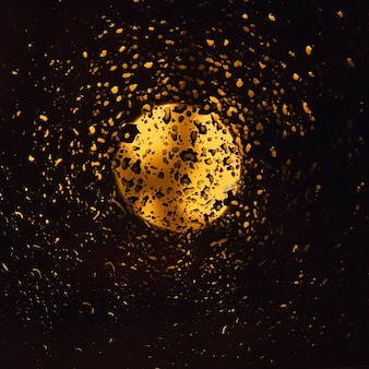 雨滴がたくさんある濡れた窓ガラスと金色に輝く月のある夜空の眺め。