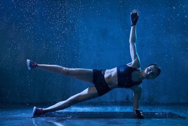 Wet woman practicing side plank exercise