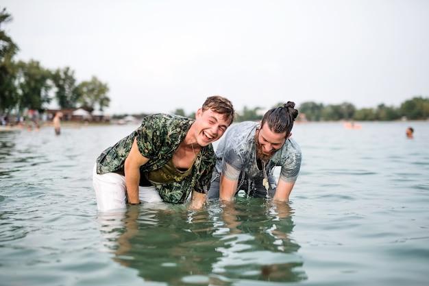 Мокрые друзья молодых людей на летнем фестивале, стоя в озере и глядя в камеру.