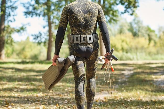 Wetのショットガンを備えたウェットスーツと足ひれのダイバーは、水狩り釣りの準備をします