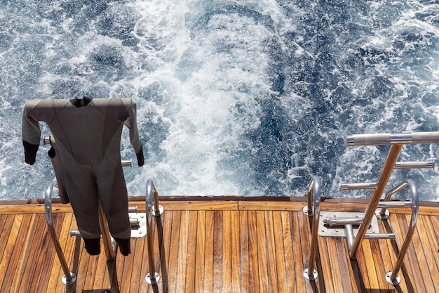 Wetsuit on a stern of the yacht while sailing on the sea. travel and vacation concept.