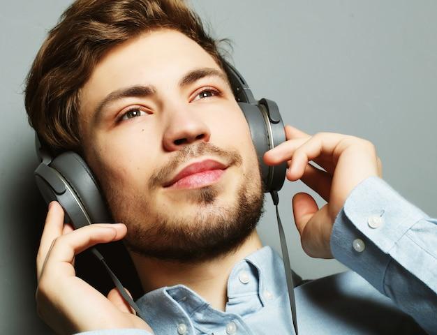 Whを笑顔彼のヘッドフォン広告を調整する幸せな若いスタイリッシュな男