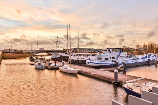 Причал с парусниками и кораблями, расположенными в волнистом канале на фоне облачного закатного неба осенним вечером