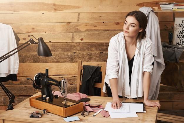 Какой прекрасный день, чтобы создать что-то необычное. портрет кавказских дизайнер работает в мастерской, опираясь на стол, глядя в сторону с мечтательным выражением, стоя возле швейной машины