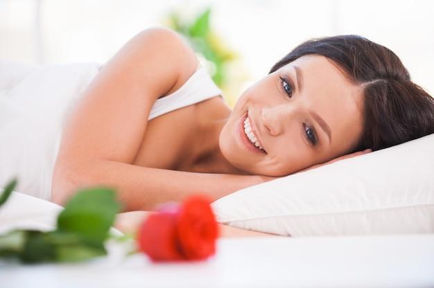 아름다운 아침입니다. 빨간 장미와 함께 침대에 누워 있는 아름 다운 젊은 여자의 측면 보기