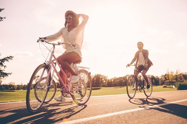 정말 좋은 날! 도로를 따라 자전거를 타고 행복해 보이는 젊은 사람들의 낮은 각도 보기