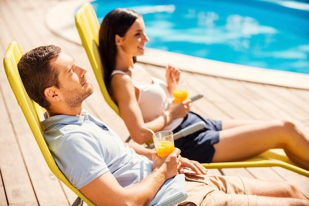 Какой хороший день! вид сбоку красивой молодой пары, держащей коктейли и улыбающейся, сидя на шезлонгах у бассейна
