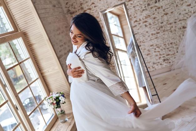이 얼마나 사랑스러운 드레스인가! 실크 목욕 가운을 입은 매력적인 젊은 여성이 웨딩드레스를 입고 창가에 서서 웃고 있다