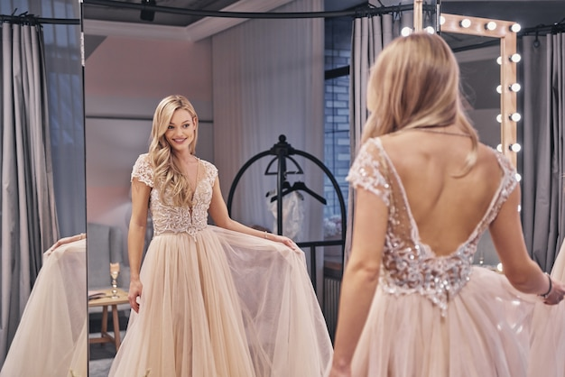 정말 멋진 드레스입니다. 웨딩 드레스를 입고 신부 가게의 거울 앞에 서서 웃고 있는 아름다운 젊은 여성